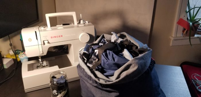 Fabric scraps in bag and glass jar next to a sewing machine